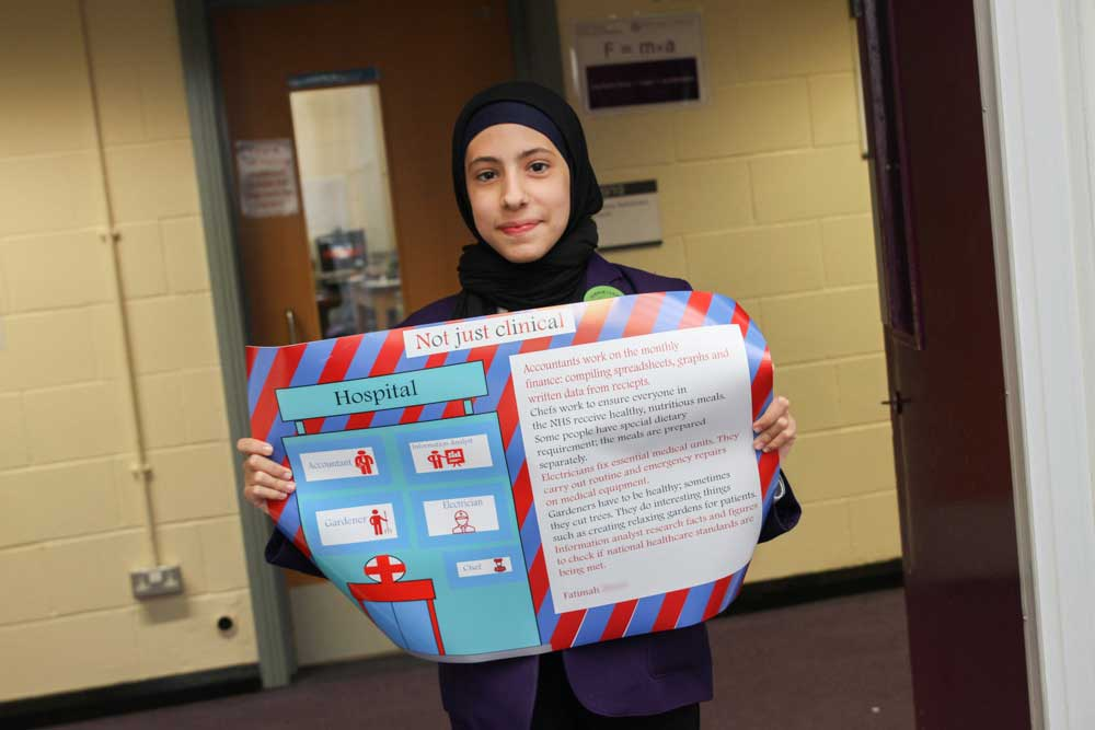 Fatimah proudly shows off her winning poster design for an NHS Careers Hub competition