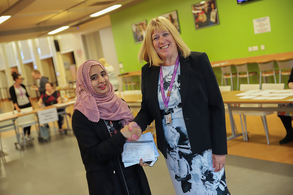 Sabbah (left) celebrates two distinctions and a merit with Academy Headteacher, Mrs E Hole (right). She'll be going on to study Psychology at the University of Salford
